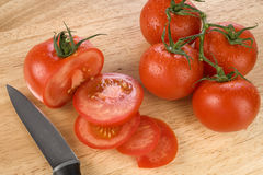 Fresh tomatoes on chopping board Stock Photos