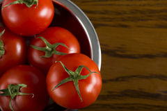 Fresh tomatoes. Close up of some fresh cherry tomatoes in metal bowl on wooden background Stock Photos
