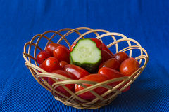 Fresh tomatoes with cucumber in a basket on a blue background Stock Images