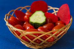 Fresh tomatoes with cucumber in a basket on a blue background Royalty Free Stock Images