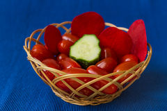 Fresh tomatoes with cucumber in a basket on a blue background Stock Photography