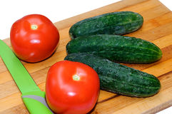 Fresh tomatoes and cucumbers on wooden Board for cutting.  Royalty Free Stock Images