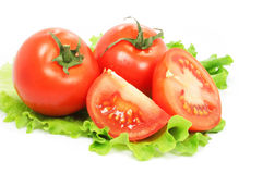 Fresh tomatoes with cut on sheet of salad Stock Photo
