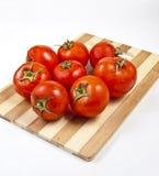 Fresh tomatoes on a cutting board. Fresh tomatoes on a wooden cutting board ,  on white background Royalty Free Stock Image