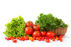 Fresh tomatoes and different herbs in a wicker basket. Royalty Free Stock Images