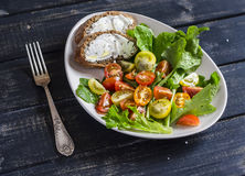 Fresh tomatoes and garden herbs salad and cheese sandwich on a white ceramic plate on dark wooden background. Stock Photography