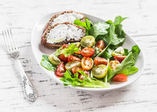 Fresh tomatoes and garden herbs salad and cheese sandwich on a white ceramic plate on a light wooden background. Stock Photography