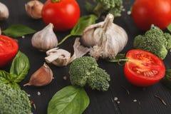 Fresh tomatoes and garlic closeup on dark rustic wood Stock Photos