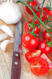 Fresh tomatoes, garlic and old knife Royalty Free Stock Photography