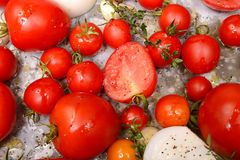 Tomatoes, onions, garlic and herbs ready for roasting Royalty Free Stock Image