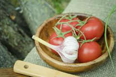 Fresh tomatoes and garlic in wooden bowl. Natural healthy food concept Royalty Free Stock Photo