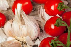 Tomatoes and garlic. Fresh tomatoes and gloves of garlic on the wood royalty free stock photography