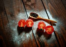Fresh tomatoes with green basil on a black stone background royalty free stock photo