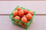 Fresh tomatoes in green plastic basket Royalty Free Stock Photo