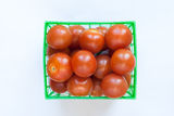 Fresh tomatoes in green plastic basket Royalty Free Stock Image