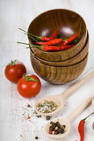 Fresh tomatoes and hot chili peppers in a wooden bowl and  spoon Stock Image