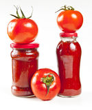 Fresh tomatoes on jars. Fresh tomatoes stacked on two jars of homemade tomato sauce, on white background Royalty Free Stock Photo