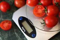 Fresh tomatoes on kitchen scales weighing Stock Image