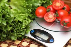 Fresh tomatoes on kitchen scales weighing Royalty Free Stock Image