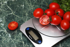 Fresh tomatoes on kitchen scales weighing Stock Photo