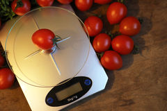 Fresh tomatoes on kitchen scales weighing Stock Photography