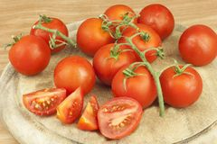 Fresh tomatoes on the kitchen table. Tomatoes on a wooden cutting board. Domestic cultivation of vegetables. Stock Photography