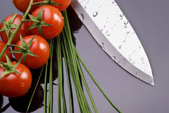 Fresh tomatoes and knife. Fresh wet tomatoes chive and knife stock photography