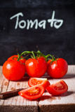 Fresh tomatoes, knife and blackboard Stock Images