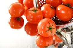 Fresh tomatoes on the mirror with strainer. Fresh wet tomatoes on the mirror with strainer royalty free stock image