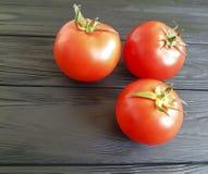 Fresh natural tomatoes whole on a black wooden antioxidant ingredient vegetarian harvest. Fresh tomatoes natural on a black wooden summer harvest vegetarian Royalty Free Stock Photo