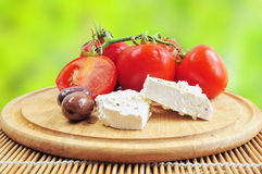 Fresh tomatoes, olives and white cheese. Closeup of fresh tomatoes, olives and white cheese on wooden board Royalty Free Stock Images