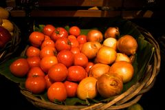 Fresh tomatoes and onions basket Stock Photography