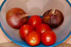 Fresh tomatoes with onions in the sieve. And on wooden table Stock Photo
