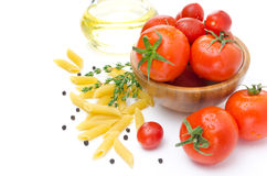 Fresh tomatoes, pasta penne, olive oil and spices on a white Stock Image