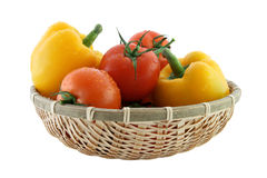 Fresh tomatoes and pepper in the basket. Fresh tomatoes and pepper in the straw basket Stock Images