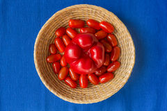 Fresh tomatoes with red paprika in a basket on a blue background Royalty Free Stock Photography