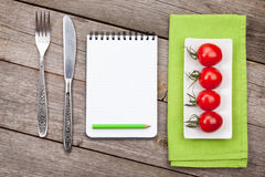 Fresh tomatoes, silverware and notepad for copy space Stock Images
