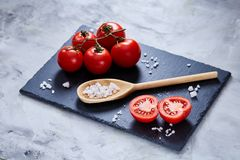 Fresh tomatoes and a spoon of salt on black stony board over white background, close-up, selective focus. stock photography