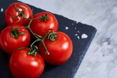 Fresh tomatoes and a spoon of salt on black stony board over white background, close-up, selective focus. stock photos