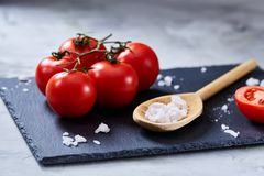 Fresh tomatoes and a spoon of salt on black stony board over white background, close-up, selective focus. royalty free stock image