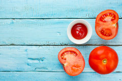 Fresh tomatoes and tomato sauce on blue wooden background Stock Photos