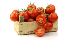 Fresh tomatoes on the vine and a cut one Royalty Free Stock Photos