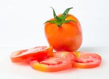 Fresh tomatoes on white chopping block. Fresh tomatoes with water drops on white chopping block Royalty Free Stock Photos