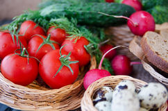 Fresh tomatoes in a wicker basket. On a background of fresh vegetables and eggs Stock Images