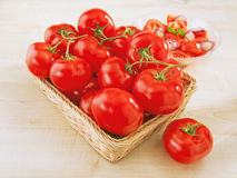 Fresh tomatoes in a wicker basket on table. And a plate with salad royalty free stock images