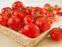 Fresh tomatoes in a wicker basket on table. And a plate with salad royalty free stock photo