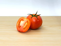 Fresh tomatoes on wooden background. The fresh tomatoes on wooden background Stock Images