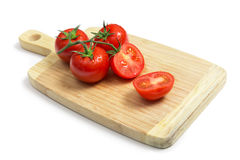 Fresh tomatoes on wooden chopping board Royalty Free Stock Images