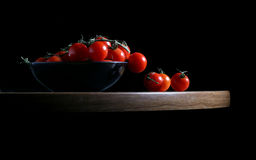 Fresh Tomatos. Red cherry tomatos in black bowl on black background royalty free stock photos