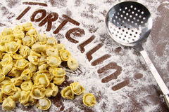 Fresh tortellini and utensil with flour on table Stock Photography